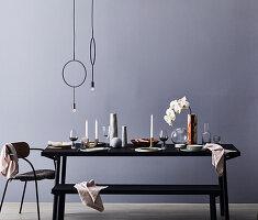 Gedeckter Tisch mit Vasen, Orchidee und Kerzen, darüber Pendelleuchte