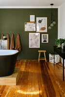 Comfortable bathroom with wooden floor and green accent wall