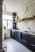 Fitted kitchen with dark cabinets and tiled wall