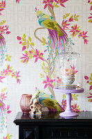 Rose in teacup under glass cover and bird ornament against wallpaper with bird motif