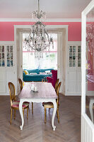 Dining table and antique chairs below chandelier