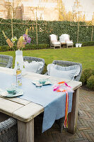 Wooden table and rattan chairs on terrace