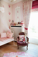 Bed with bed crown and armchair in girl's bedroom
