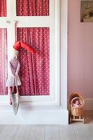 Rag doll hanging from wardrobe door in girl's bedroom