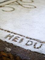Handmade pebble mosaic lettering in concrete floor