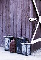 Frosty lanterns outside wooden house in winter