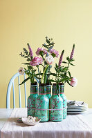 Carnations, veronica and eucalyptus in empty bottles used as vases
