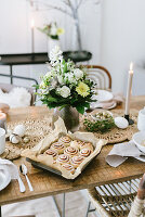 A tray on buns and a bouquet of flowers on a table laid for an Easter meal