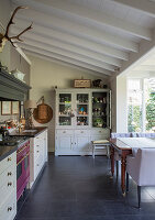 A classic eat-in kitchen in shades of grey with a conservatory and a beamed ceiling