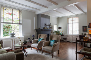 Grey winged armchairs in a classic living room with a fireplace