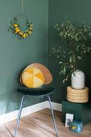 Yellow velvet cushion on retro chair against dark green wall