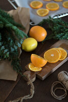 Sliced oranges on chopping board next to evergreen branches
