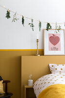 Garland of fairy lights and various twigs above bed