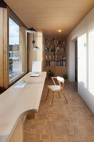 Long desk in narrow study furnished in pale wood