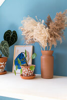 Pampas grass in clay vase and Chinese money plant in painted terracotta pot