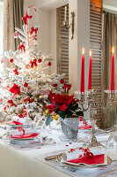 Festively set table and Christmas tree decorated in red and white
