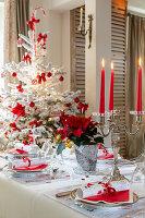 Festlich gedeckter Tisch und Weihnachtsbaum in Rot und Weiß