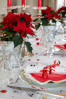 Table festively set in red and white decorated with poinsettias