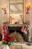 Various Christmas stockings hung on antique open fireplace