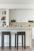 Angular barstools at island counter in beige modern kitchen