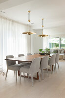 Pale grey upholstered chairs at long dining table in open-plan interior