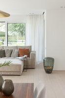 Floor vase next to modern sofa in pale grey living room