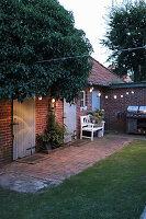 Courtyard garden lit by fairy lights at twilight