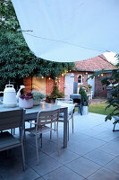 Table and chairs on terrace in courtyard garden at twilight