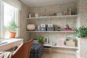 Regalbretter, Polsterhocker und Schreibtisch mit Lederstuhl im Zimmer mit Blumentapete