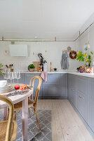 Runder Esstisch aus Holz und Unterschränke mit grauen Fronten in der Küche