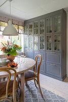 Grau lackierte Vitrine und runder Esstisch aus Holz in der Küche
