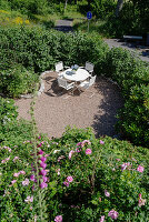A round table and chairs on a terrace in a sunny garden