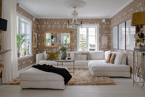 A white upholstered sofa in a living room with floral wallpaper