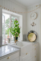 A white kitchen work surface with a sink in front of the window