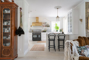 An antique crockery cupboard in a passageway with a breakfast bar in a white kitchen
