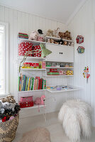 An open shelf in a girl's bedroom with white wood panelling
