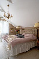 A brass double bed in an attic bedroom
