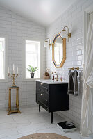 A washbasin and a gold-framed mirror in a bathroom with white subway tiles