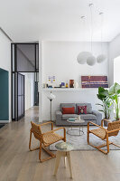 A lounge with an upholstered sofa and vintage armchairs in an open-plan living room