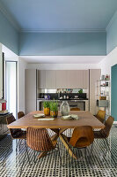 A dining area with a large wooden table and classic chairs in front of a fitted kitchen