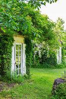 Versteckter Eingang mit Glastür im Garten
