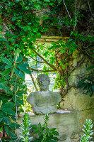 Bewaschsene Steinmauer mit antiker Büste