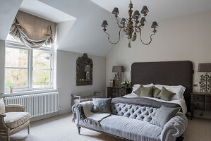 Master bedroom with buttoned back sofa, chandelier, table lamps and headboard