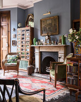 Arts and Crafts style revolving bookcase with 1930s drapers unit and colonial style chair in drawing room