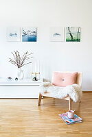 Magazines and cup next to wooden armchair with sheepskin rug and cushion in living room