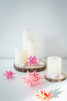 White pillar candles on wooden discs with origami 3D stars