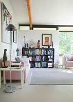 Pink sofa and modular shelving in living room with glass wall