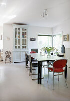 Old glass-fronted cabinet and modern dining set in eclectic dining room