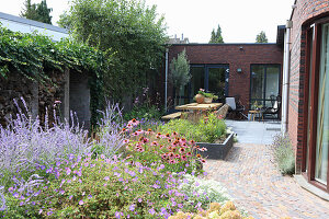 A garden path leading along a flowerbed to a terrace