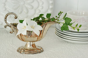 Silver gravy boat decorated with ivy tendrils and white campanula flowers